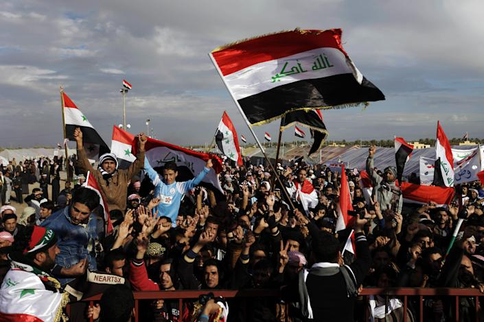 FILE - In this file photo taken in Wednesday, Jan. 9, 2013, Protesters chant slogans against Iraq's Shiite-led government as they wave national flags during a demonstration in Ramadi, 70 miles (115 kilometers) west of Baghdad, Iraq. Iraqi police dismantled tents and cleared a sit-in camp site after Sunnis in a flashpoint western city ended their months-long protest following a deal with the country's Shiite-led government, an official said Monday. (AP Photo/Khalid Mohammed, File)