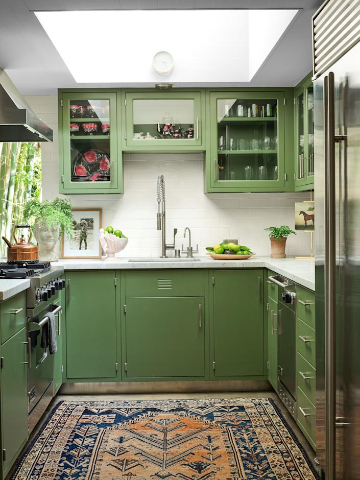 The kitchen cabinetry is painted in Benjamin Moore's Alligator Alley. Range, hood, and dishwasher by Viking; refrigerator by Sub-Zero; antique Persian rug.
