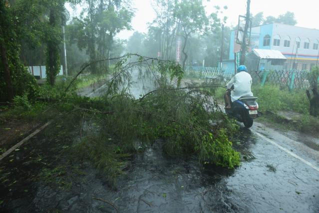 A man rides his bike past fallen tree branches along a road ahead of the expected landfall of cyclone Amphan in Digha, West Bengal, on May 20, 2020. - India and Bangladesh began evacuating more than two million people on May 18 as a cyclone barrelled towards their coasts, with officials racing to ready extra shelters amid fears of coronavirus contagion in cramped refuges. (Photo by Dibyangshu SARKAR / AFP) (Photo by DIBYANGSHU SARKAR/AFP via Getty Images)