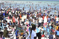 Hundreds of people crowd the Jomo Kenyatta public beach on Christmas day in Mombasa, Kenya, Friday, Dec. 25, 2020. Despite the World Health Organization's guidelines, many of the holiday makers had no masks on their faces or kept social distance which might increase the COVID-19 pandemic infections. The public beach had been closed down during this year's Easter holidays due to the COVID-19 pandemic but was recently opened to members of the public. (AP Photo)