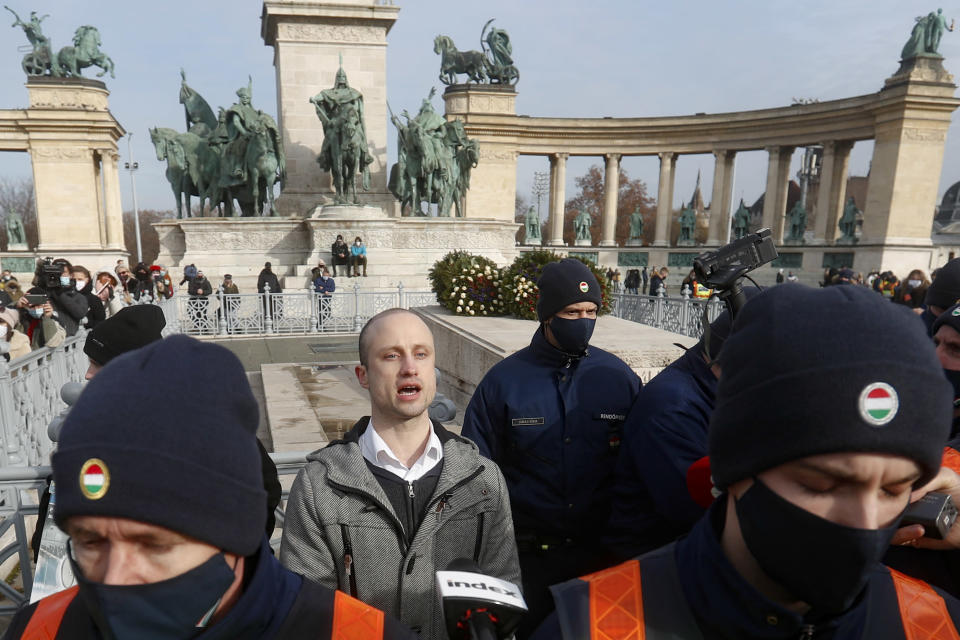 Aron Ecsenyi, the protest organizer, speaks to media standing behind a police line, while his ID is checked in a hospitality sector workers protest, in Budapest, Hungary, Sunday, Jan. 31, 2021. Protesters gathered at a central square in Hungary's capital of Budapest on Sunday demanding a rethinking of the country's lockdown restrictions. As the lockdown limiting restaurants to take-away service approaches the three-month mark, many business owners complain that they have received little to none of the government's promised financial assistance while other businesses like shopping malls and retail stores have been permitted to remain open. (AP Photo/Laszlo Balogh)
