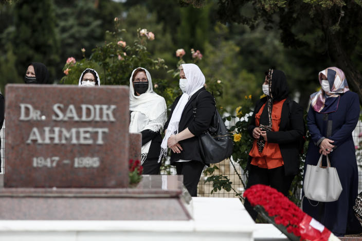 """Women stand around the grave of Ahmet Sadik, who was an MP at the Greek parliament, at a muslim cemetery at Komotini town, in northeastern Greece, Sunday, May 30, 2021. Greece's prime minister said Friday his country is seeking improved ties with neighbor and longtime foe Turkey, but that the onus is on Turkey to refrain from what he called """"provocations, illegal actions and aggressive rhetoric."""" (AP Photo/Giannis Papanikos)"""