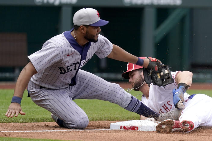 Kansas City Royals' Andrew Benintendi, right, is tagged out by Detroit Tigers third baseman Jeimer Candelario as he tried to steal third base during the fourth inning of a baseball game Sunday, May 23, 2021, in Kansas City, Mo. (AP Photo/Charlie Riedel)