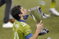 Seattle Sounders' Nicolas Lodeiro holds the championship trophy to his lips after the team beat Minnesota United 3-2 in an MLS playoff Western Conference final soccer match, Monday, Dec. 7, 2020, in Seattle. (AP Photo/Ted S. Warren)