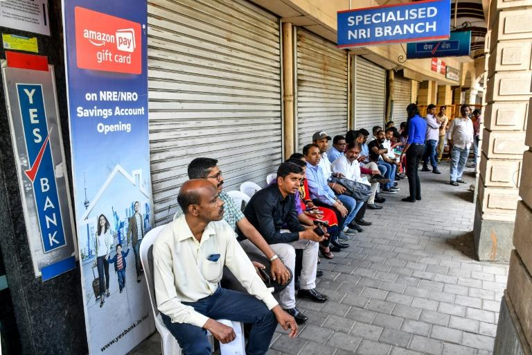 Customers wait outside a Yes Bank branch in Mumbai after a run on deposits