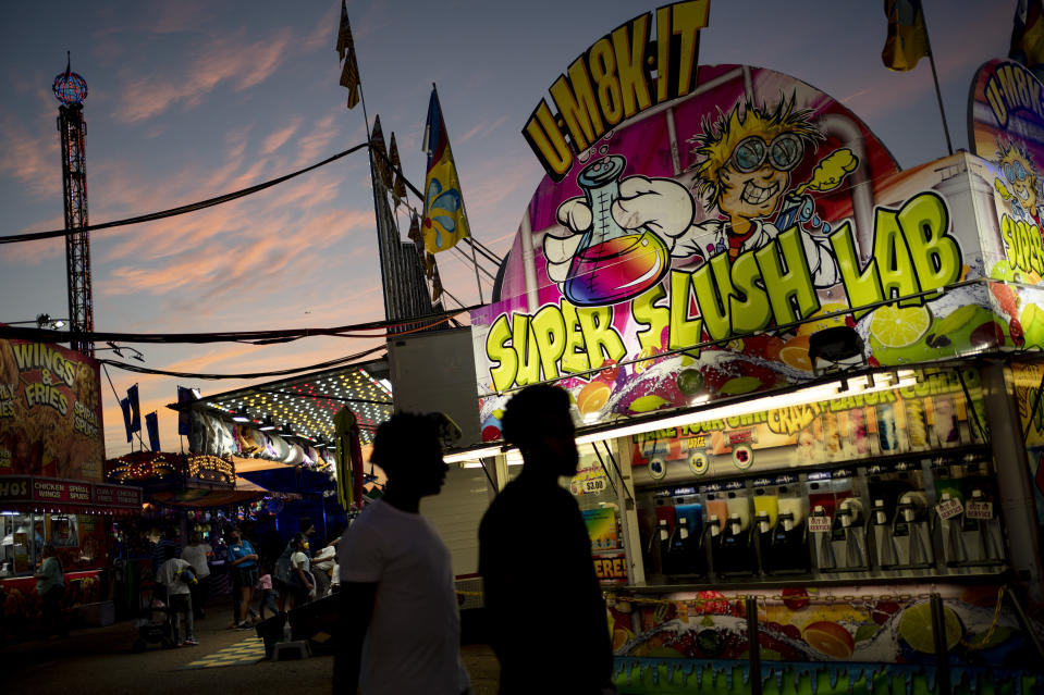 Visitors walk among illuminated booths at the Mississippi State Fair, Wednesday, Oct. 7, 2020, in Jackson, Miss. At the fair, which is held every year in October and attracts people from across the racial spectrum, the vast majority of Black people are wearing masks. Most white people do not. (AP Photo/Wong Maye-E)
