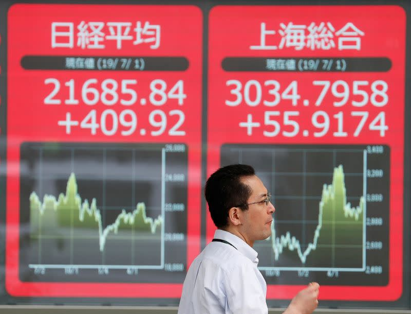 A man walks past an electric screen showing Japan's Nikkei and Shanghai Stock Exchange markets' indices outside a brokerage in Tokyo