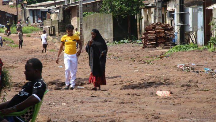 Guinean wrestler Fatoumata Yarie Camara walks with her mother near her house in Conakry, Guinea, Monday July 19, 2021. A West African wrestler's dream of competing in the Olympics has come down to a plane ticket. Fatoumata Yarie Camara is the only Guinean athlete to qualify for these Games. She was ready for Tokyo, but confusion over travel reigned for weeks. The 25-year-old and her family can't afford it. Guinean officials promised a ticket, but at the last minute announced a withdrawal from the Olympics over COVID-19 concerns. Under international pressure, Guinea reversed its decision. (AP Photo/Youssouf Bah)