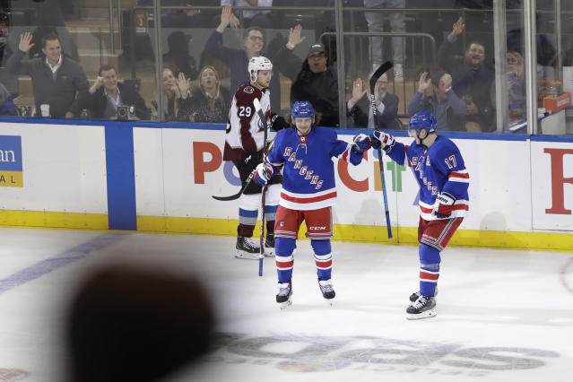 New York Rangers' Artemi Panarin (10) celebrates with Jesper Fast (17) after scoring an empty-net goal as Colorado Avalanche's Nathan MacKinnon (29) skates past during the third period of an NHL hockey game Tuesday, Jan. 7, 2020, in New York. The Rangers won 5-3. (AP Photo/Frank Franklin II)