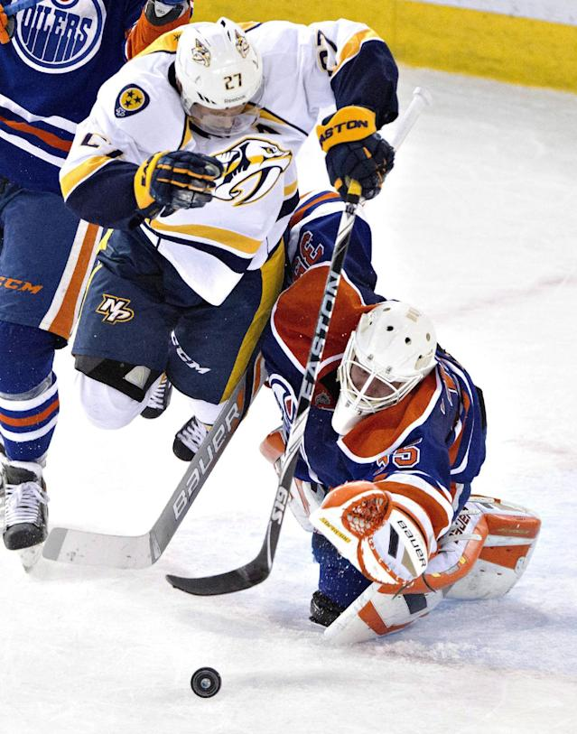 Nashville Predators' Patric Hornqvist (27) crashes into Edmonton Oilers goalie Viktor Fasth (35) as Fasth makes a save during the second period of an NHL hockey game Tuesday, March 18, 2014, in Edmonton, Alberta. (AP Photo/The Canadian Press, Jason Franson)