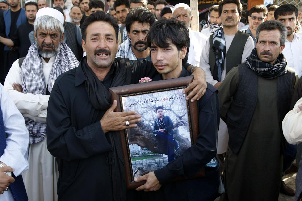 <p>Afghan people gather to stage a demonstration against Afghan Government due to increasing security issues as they carry photographs those who lost their lives on Tuesday evening after an assault to a mosque, in Herat, Afghanistan on August 02, 2017. (Photo by Mir Ahmad Firooz/Anadolu Agency/Getty Images) </p>