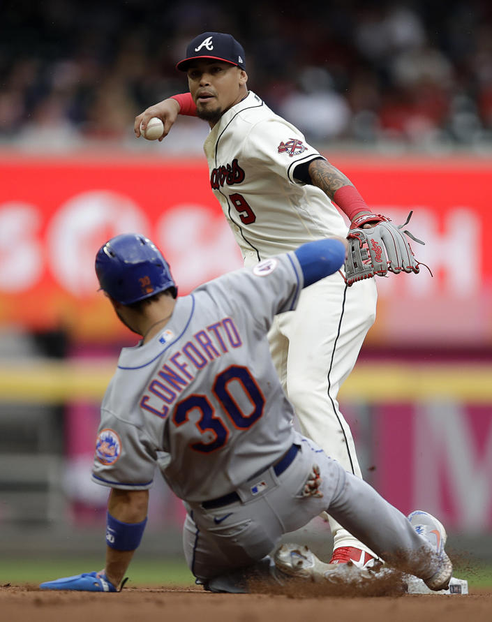 Atlanta Braves' Orlando Arcia, top, prepares to throw over New York Mets' Michael Conforto (30) to complete a double play in the seventh inning of a baseball game Sunday, Oct. 3, 2021, in Atlanta. Mets' Pete Alonso was out at first base. (AP Photo/Ben Margot)