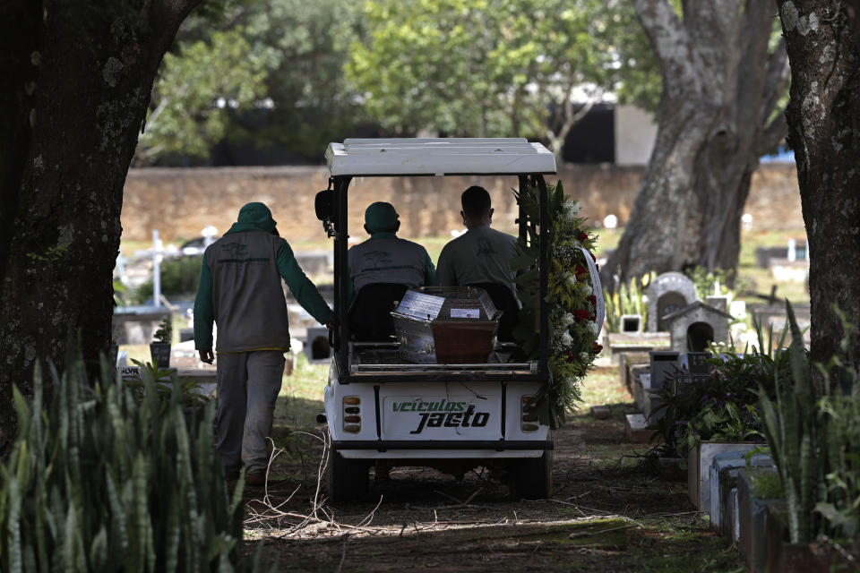 Cemetery workers transport the coffin that contains the remains of Jose Valdelirio believed to have died from the new coronavirus, to a burial site at the Campo da Esperanca cemetery in the Taguatinga neighborhood of Brasilia, Brazil, Wednesday, March 3, 2021. The number of COVID-19 cases in Brazil is still surging, with a new record high of deaths reported on Tuesday. (AP Photo/Eraldo Peres)
