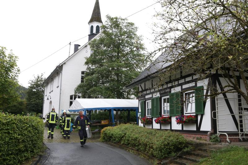 In this Sunday, Sept. 8, 2019 photo fire fighters are seen after an explosion at a village festival in Freudenberg, Germany. Authorities say 14 people have been injured, five of them with life-threatening burns, during an explosion at a village festival in western Germany. Police told German news agency dpa that it appears likely that oil inside a big frying pan caused the explosion at the local 'Backesfest' (bakery festival) that was attended by about 100 people. (Berthold Stamm/dpa via AP)