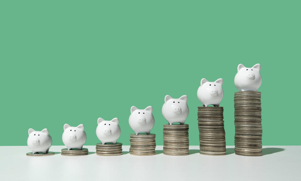Little white piggy banks standing on top of 7 stacks of coins in ascending order on white surface, green background