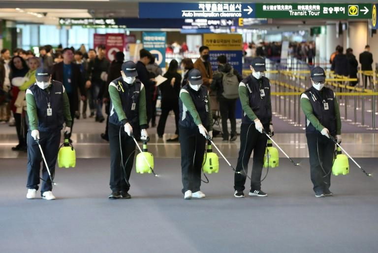 Cleaners spray disinfectant at Seoul's Incheon international airport after South Korea confirmed its first case of the SARS-like virus