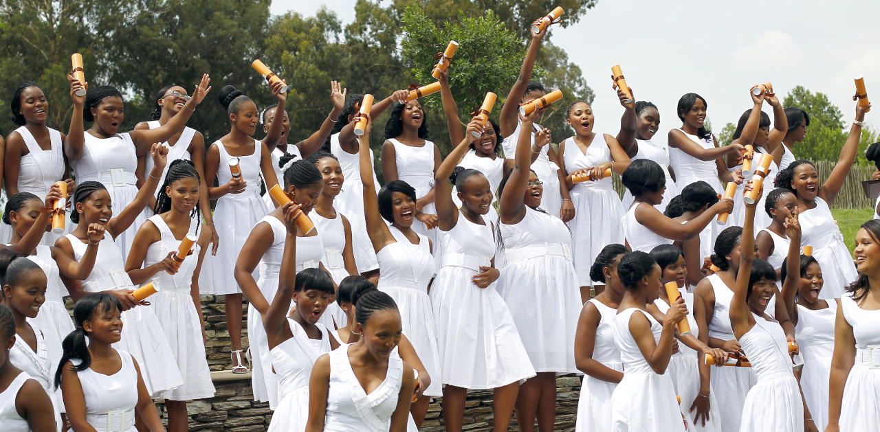 """Graduates line up for a photo opportunity after the first graduation ceremony at Oprah Winfrey's leadership academy for girls in Henley on Klip, South Africa, Saturday Jan. 14, 2012. Winfrey said the first students to graduate from her academy for underprivileged South African girls were """"free to soar,"""" during a graduation speech Saturday.(AP Photo/Jerome Delay)"""