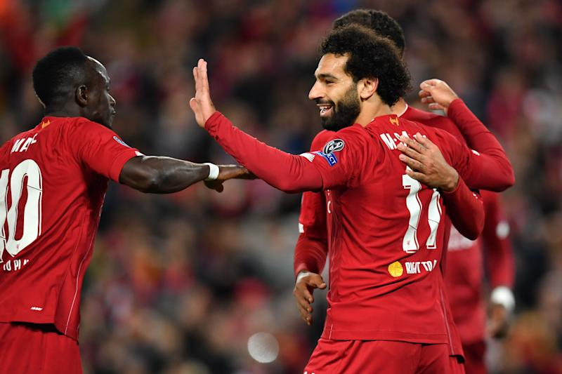 Liverpool's Egyptian midfielder Mohamed Salah (R) celebrates with Liverpool's Senegalese striker Sadio Mane (L) and Liverpool's Brazilian midfielder Roberto Firmino after scoring their fourth goal during the UEFA Champions league Group E football match between Liverpool and Salzburg at Anfield in Liverpool, north west England on October 2, 2019. (Photo by Paul ELLIS / AFP) (Photo by PAUL ELLIS/AFP via Getty Images)