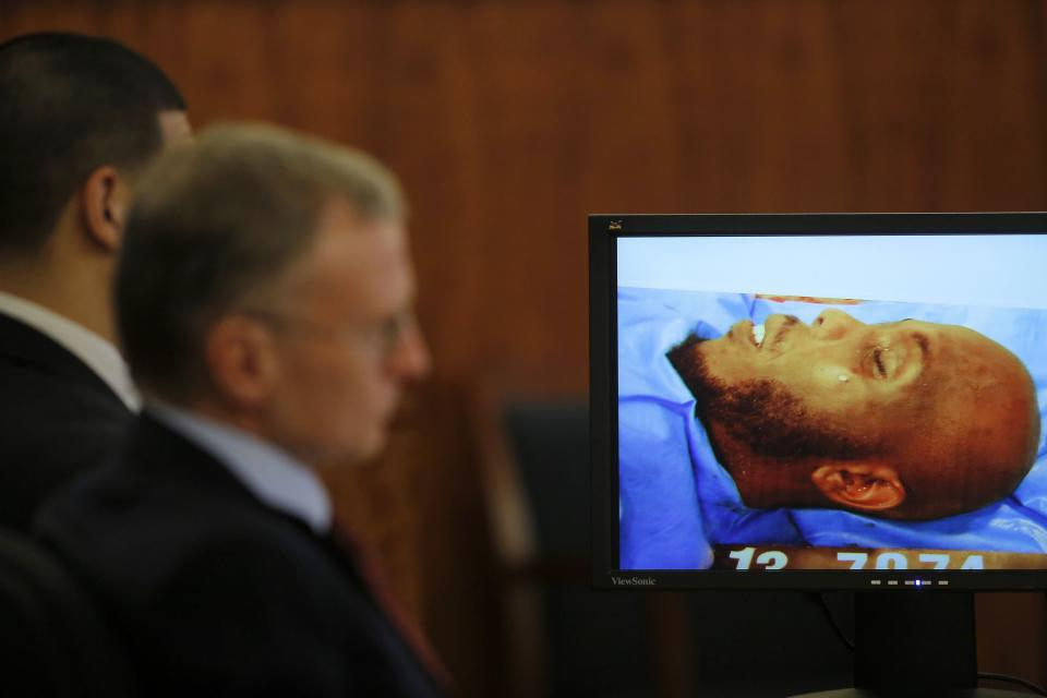 Former New England Patriots tight end Aaron Hernandez (L) and his attorney Charles Rankin sit next to an image of Odin Lloyd from the medical examiner's office during Hernandez' murder trial at Bristol County Superior Court in Fall River, Massachusetts February 4, 2015. Hernandez is accused of the murder of semi-professional football player Lloyd in 2013. REUTERS/Brian Snyder (UNITED STATES - Tags: CRIME LAW SPORT FOOTBALL)