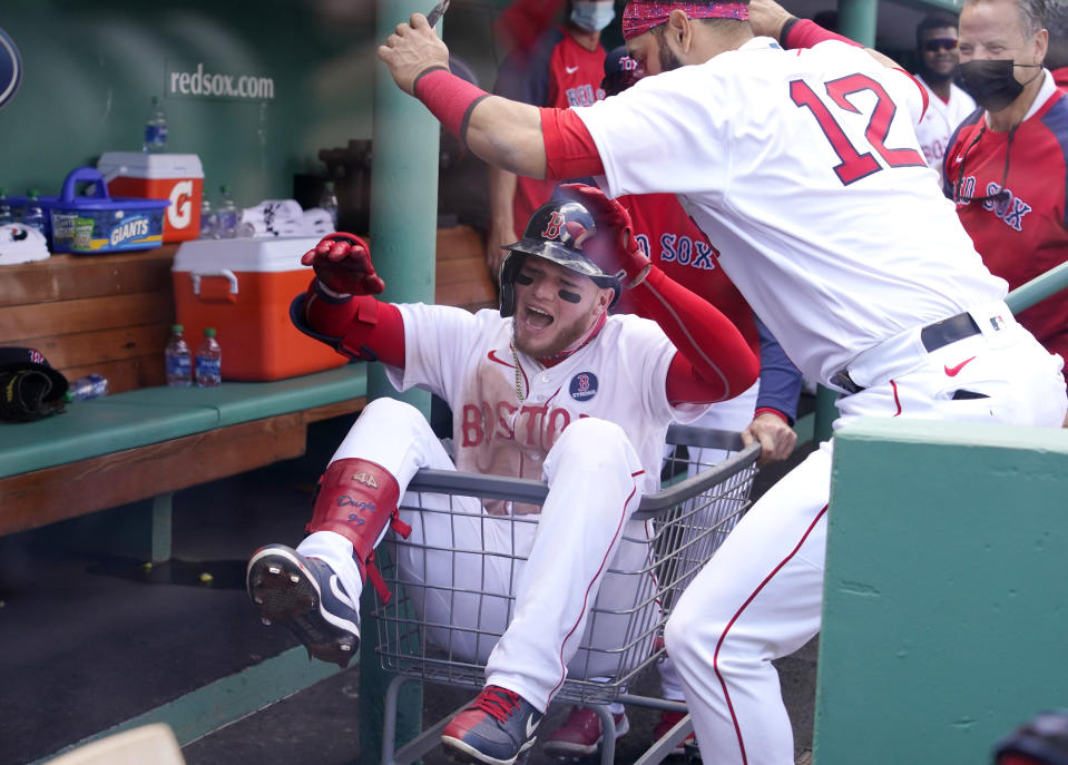 Boston Red Sox's Alex Verdugo is pushed through the dugout in a basket as he celebrates his solo home run with teammate Marwin Gonzalez (12) in the third inning of a baseball game against the Chicago White Sox at Fenway Park, Monday, April 19, 2021, in Boston. (AP Photo/Elise Amendola)