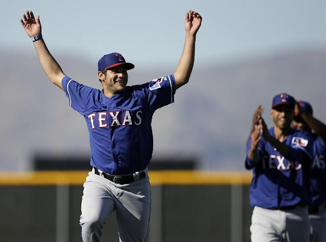 Texas Rangers' Martin Perez leads a line of pitchers in stretching before a morning workout during spring training baseball practice, Monday, Feb. 17, 2014, in Surprise, Ariz. (AP Photo/Tony Gutierrez)
