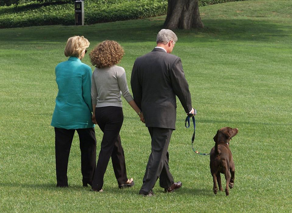 WASHINGTON, :  US President Bill Clinton (R), First Lady Hillary Clinton (L), and their daughter Chelsea (C) depart 18 August the White House in Washington, DC, with their dog Buddy on their way to a two-week vacation in Martha's Vineyard, Massachusetts.  Clinton gave a televised address 17 August to the American people from the White House regarding his testimony earlier 17 August to a federal grand jury in which he admitted to an improper relationship with former White House intern Monica Lewinsky.     (ELECTRONIC IMAGE)     AFP PHOTO     Luke FRAZZA (Photo credit should read LUKE FRAZZA/AFP via Getty Images)