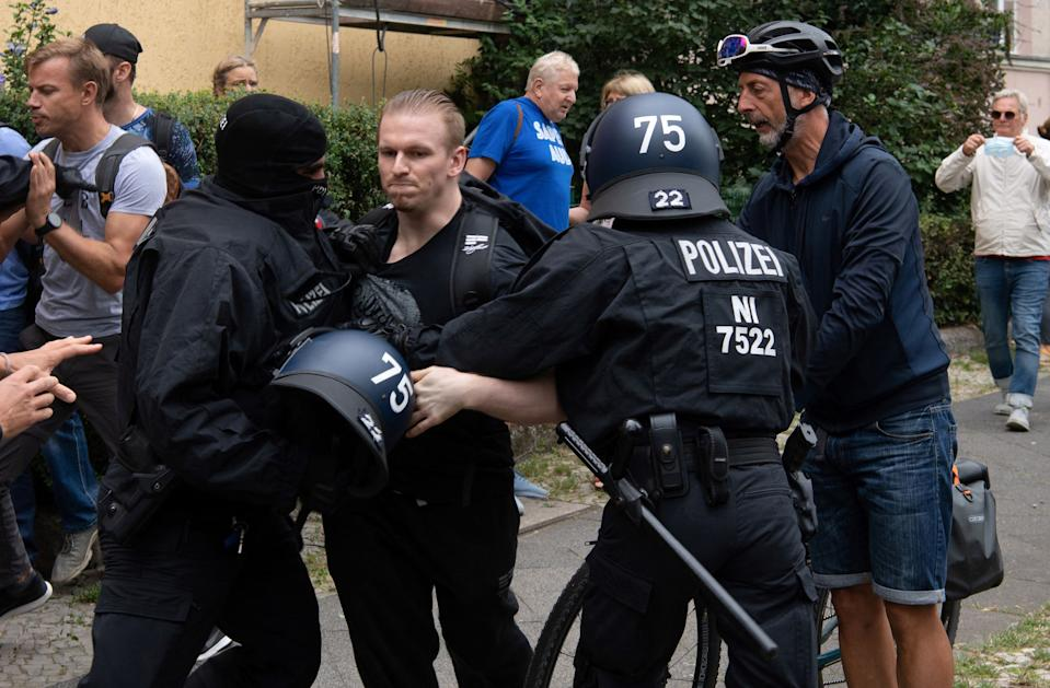 German police arrest a participant of an anti-lockdown protest in Berlin on August 1, 2021. - Berlin police clashed with Covid sceptics on August 1 after hundreds of them took to the streets despite a court-ordered protest ban over concerns participants would not respect rules on mask-wearing and social distancing. (Photo by Paul ZINKEN / AFP) (Photo by PAUL ZINKEN/AFP via Getty Images)