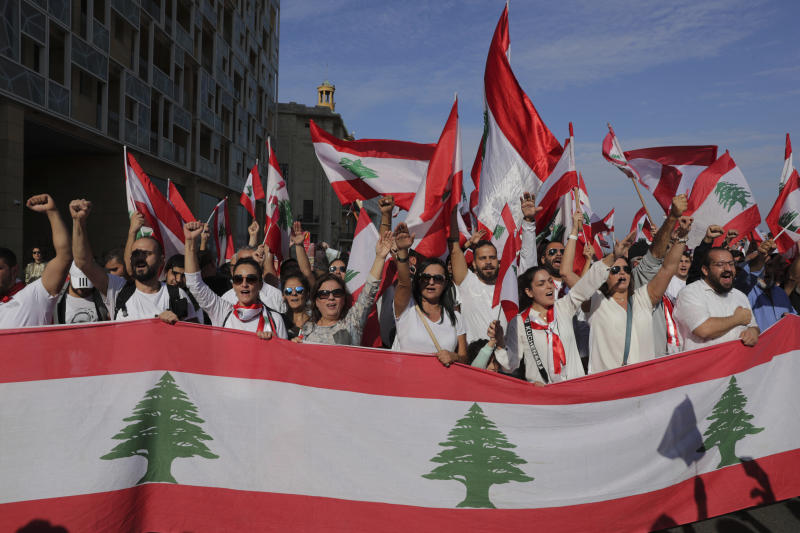 Anti-government protesters shout slogans during separate civil parade at the Martyr square, in downtown Beirut, Lebanon, Friday, Nov. 22, 2019.  Protesters gathered for alternative independence celebrations, converging by early afternoon on Martyrs' Square in central Beirut, which used to be the traditional location of the official parade. Protesters have occupied the area, closing it off to traffic since mid-October.  (AP Photo/Hassan Ammar)