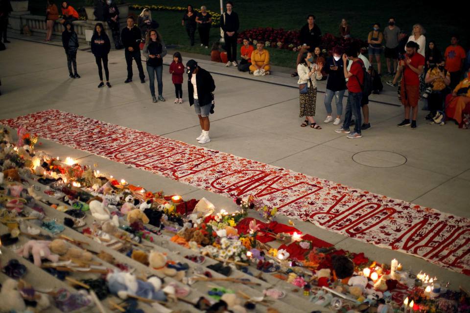 People pay respects to the victims of Canada's residential school system amid shoes, teddy bears, orange shirts and other tributes placed on the steps outside the legislature, in Victoria, Thursday, July 1, 2021. (Chad Hipolito/The Canadian Press via AP)