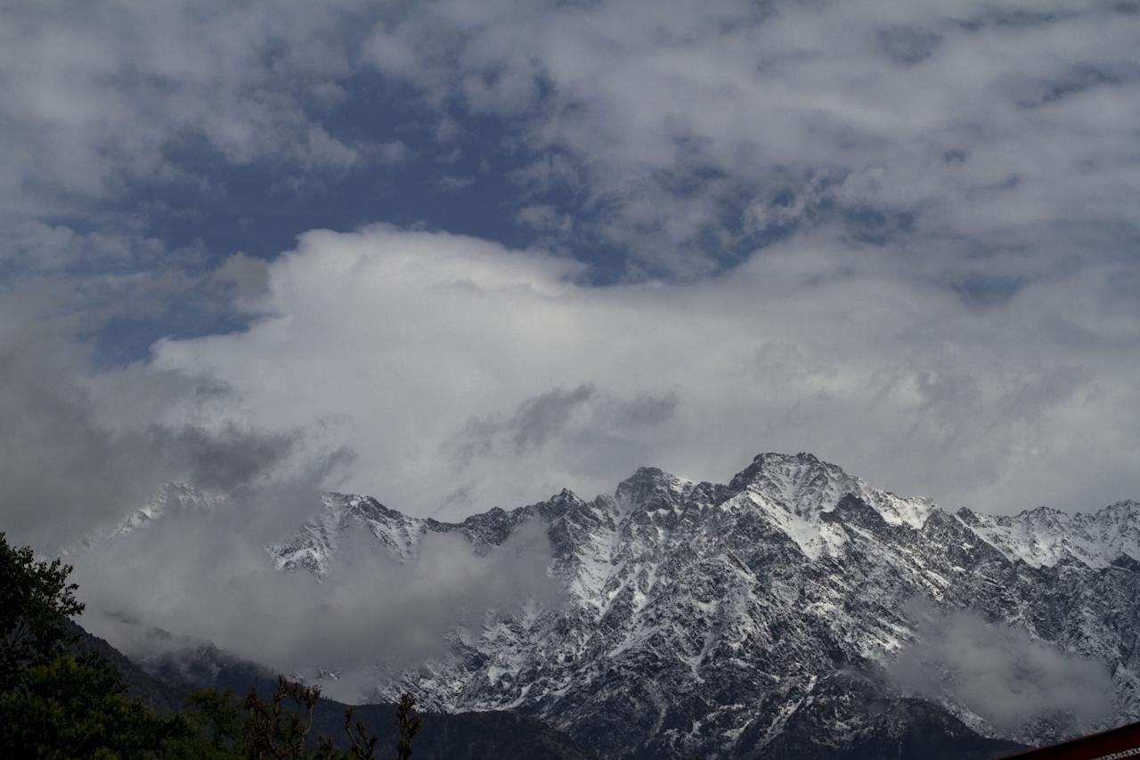 <p>The snow-covered Dhauladhar ranges with white clouds hovering over them , seen from Palamapur in Himachal Pradesh's Kangra district, on April 11, 2018. (Photo: IANS) </p>