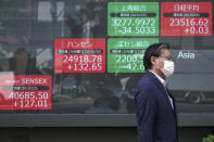 A man walks past an electronic stock board showing Japan's Nikkei 225 and other Asian indexes at a securities firm in Tokyo Monday, Oct. 26, 2020. Asian shares were little changed in muted trading Monday amid widespread uncertainty over what the U.S. presidential election will portend for markets and economic policy.(AP Photo/Eugene Hoshiko)