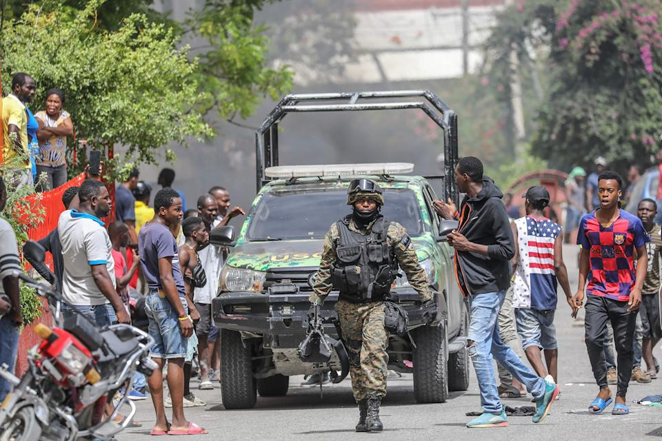 People surround police station holding suspect in assassination (AFP via Getty Images)