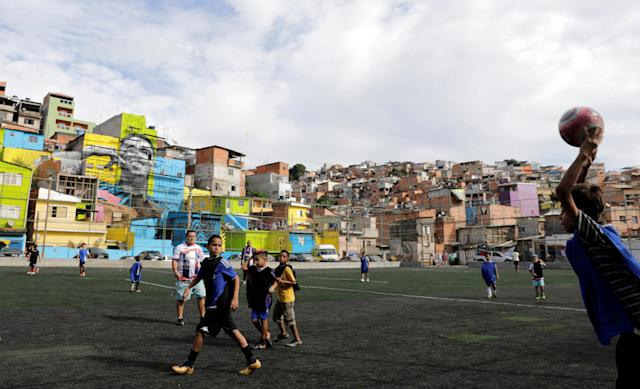 Players attend a training in a field with the image of Brazil's soccer player Gabriel Jesus in the background, painted on the walls of houses in the neighbourhood he lived in during his childhood in Sao Paulo, Brazil May16, 2018. REUTERS/Paulo Whitaker