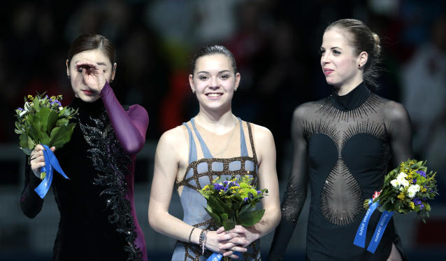 Adelina Sotnikova of Russia, centre, Yuna Kim of South Korea, left, and Carolina Kostner of Italy stand on the podium during the flower ceremony for the women's free skate figure skating final at the Iceberg Skating Palace during the 2014 Winter Olympics, Thursday, Feb. 20, 2014, in Sochi, Russia. Sotnikova placed first, followed by Kim and Kostner. (AP Photo/Ivan Sekretarev)