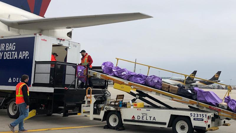 Mail bags being loaded with a conveyor onto a passenger airplane.
