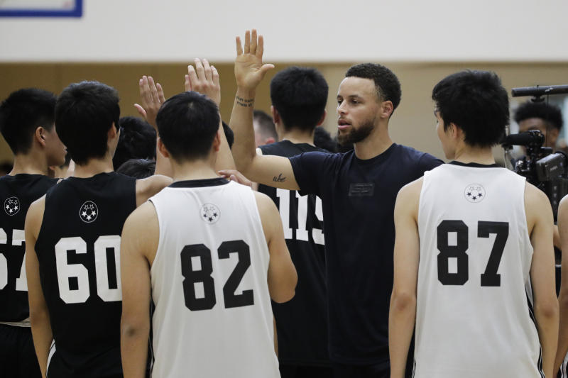 Golden State Warriors' Stephen Curry, second from right, high-fives high school basketball players after a basketball camp Sunday, June 23, 2019, in Tokyo. Curry is already looking ahead to the next challenge in his basketball career, including the chance to represent the United States at next year's Tokyo Olympics.(AP Photo/Jae C. Hong)