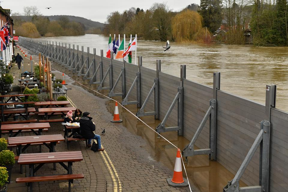 People eating in front of temporary flood defences in Bewdley, Worcestershire, in the aftermath of Storm Dennis.