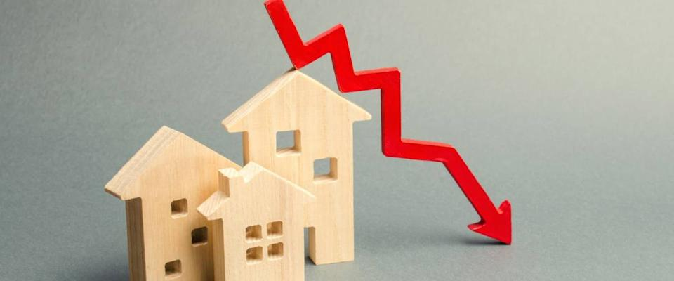 Miniature wooden houses and a red arrow down.Falling interest rates