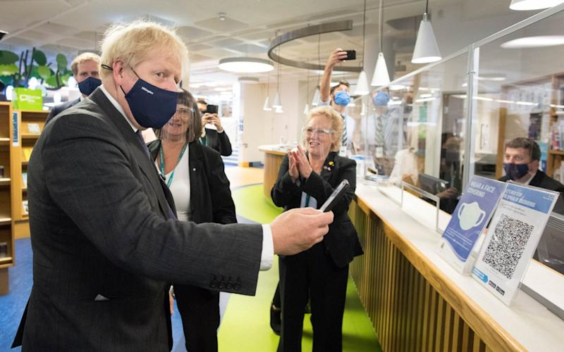 Prime Minister Boris Johnson scans his NHS Coronavirus App at Uxbridge Library during a walkabout where he met shoppers and shopkeepers in his constituency of Uxbridge, west London - Stefan Rousseau/PA
