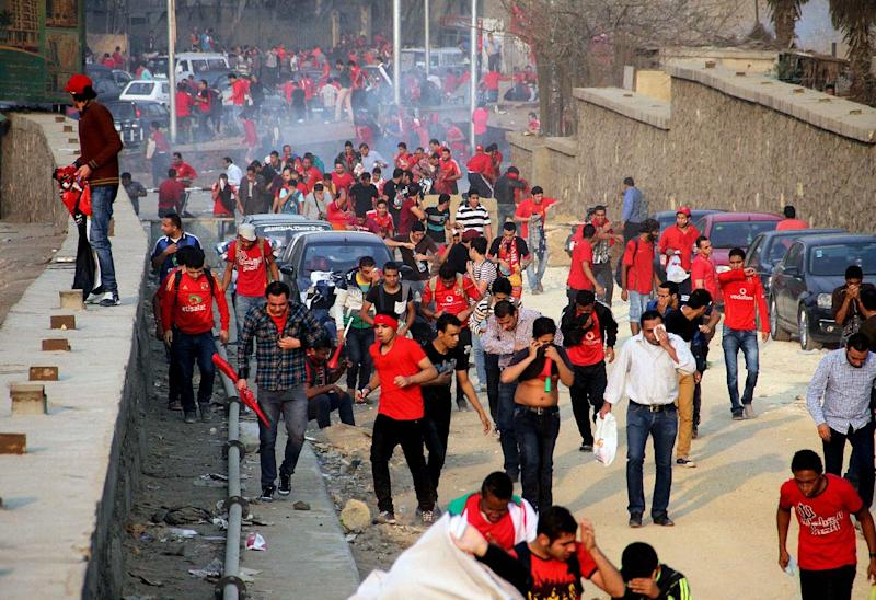 Supporters of Egyptian club Al Ahly run from tear gas during clashes with police outside a stadium ahead of the African Champions League final in Cairo, Egypt, Sunday, Nov. 10, 2013. Police used tear gas Sunday to disperse the crowd as they threw rocks and tried to push their way into the stadium, many with no tickets. (AP Photo/Mostafa Darwish)