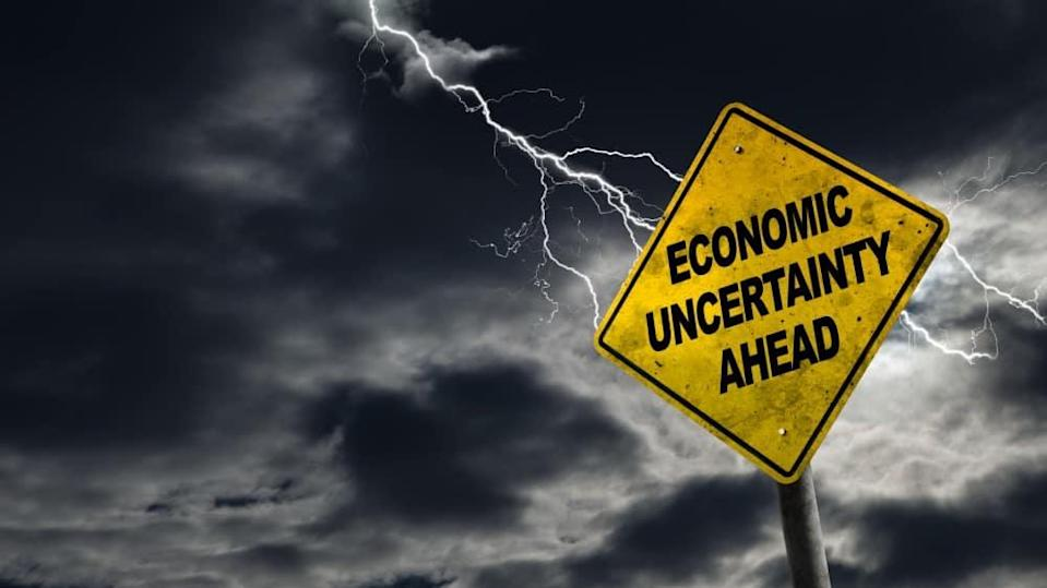 Economic Uncertainty Ahead Sign With Stormy Background