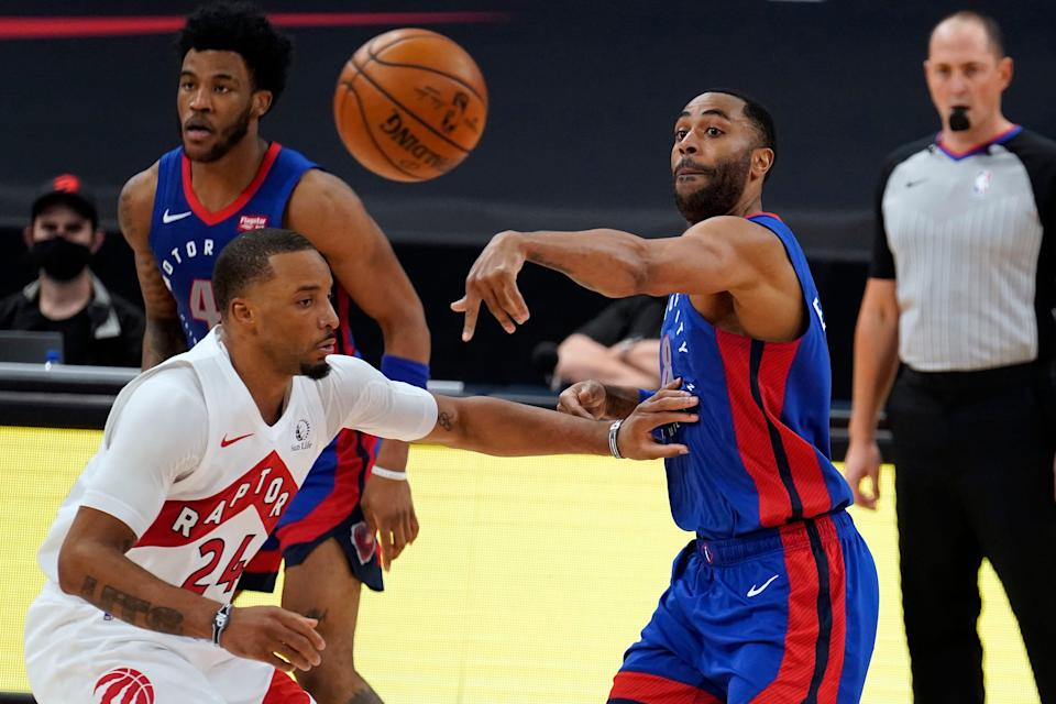 Pistons guard Wayne Ellington passes the ball over Raptors guard Norman Powell during the second half of the Pistons' 129-105 win on Wednesday, March 3, 2021, in Tampa, Florida.