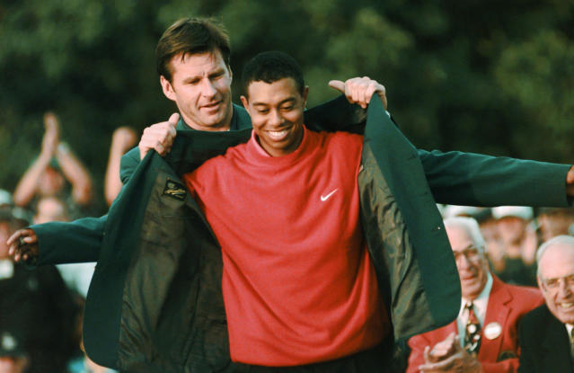 FILE - In this April 13, 1997, file photo, Masters champion Tiger Woods receives his Green Jacket from last year's winner Nick Faldo, rear, at the Augusta National Golf Club in Augusta, Ga. Woods completes an amazing journey by winning the 2019 Masters, overcoming 11 years of personal foibles and professional pain that seemed likely to be his lasting legacy. (AP Photo/Dave Martin, File)