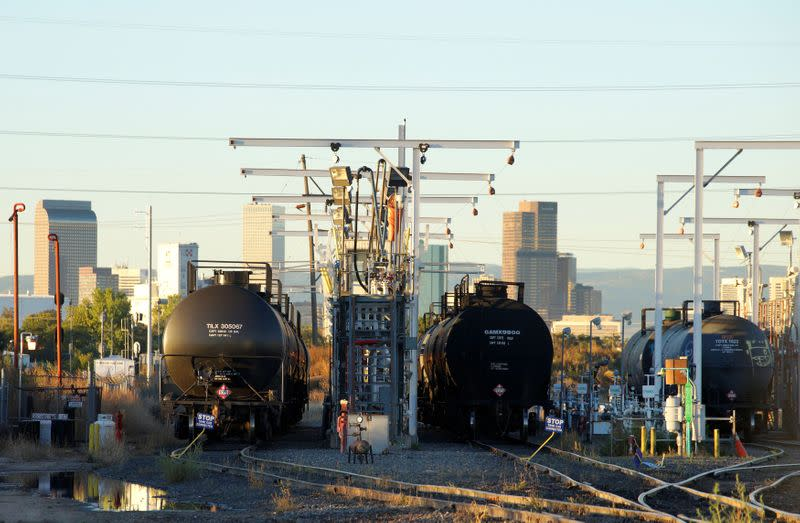 FILE PHOTO: Oil tanker railcars are parked at a filling rack at sunrise with the Denver downtown skyline in the background