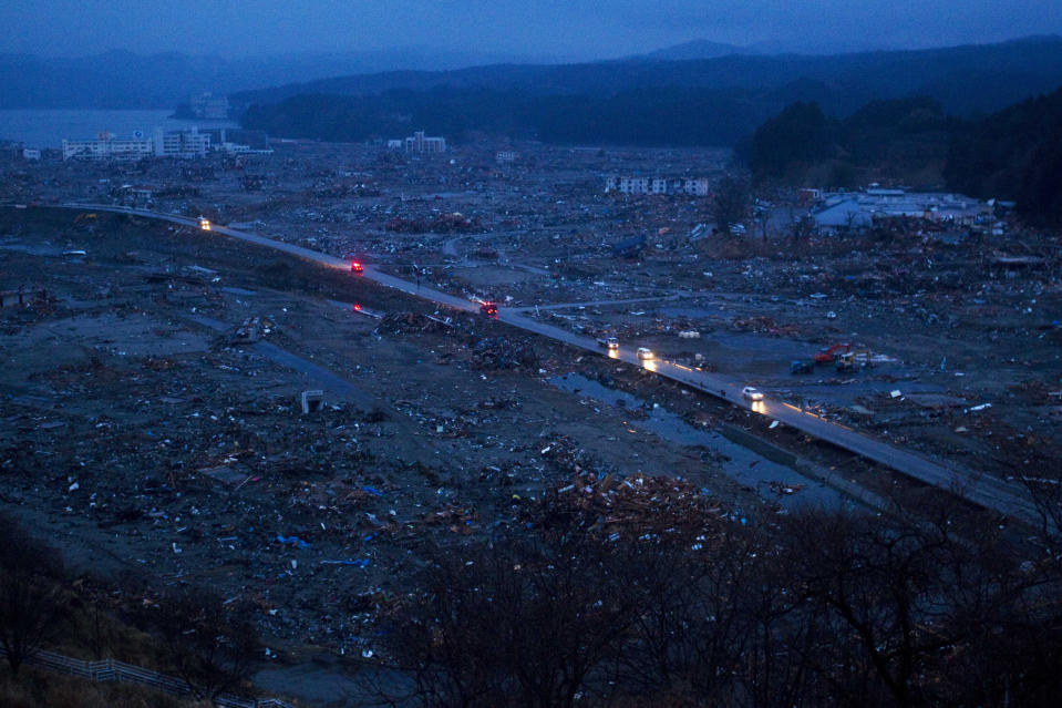 In this March 15, 2011, file photo, vehicles pass through the ruins of the leveled city of Minamisanriku, Miyagi Prefecture, northeastern Japan, four days after the Tsunami devastated the area. (AP Photo/David Guttenfelder, File)