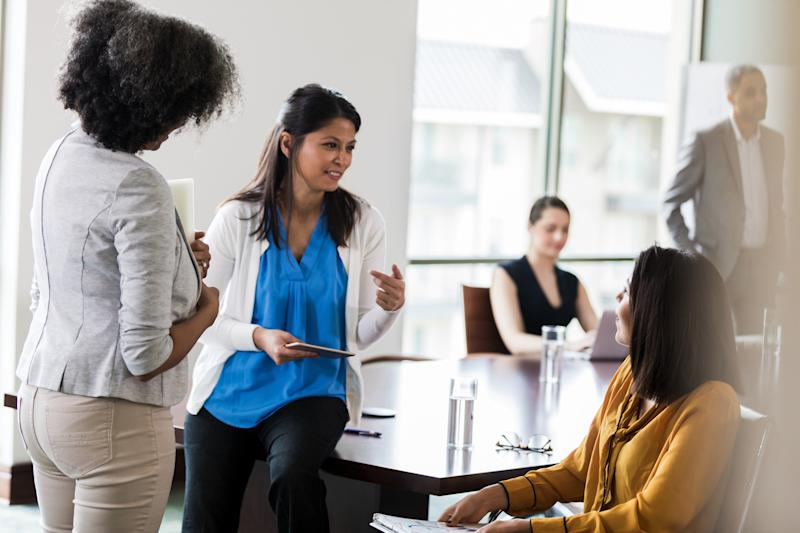 Confident businesswomen participate in brainstorming session after a meeting.