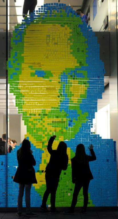 The face of Apple co-founder and former CEO Steve Jobs is created with adhesive notes on the window of an Apple Store in Munich on October 18, 2011 (AFP/CHRISTOF STACHE)