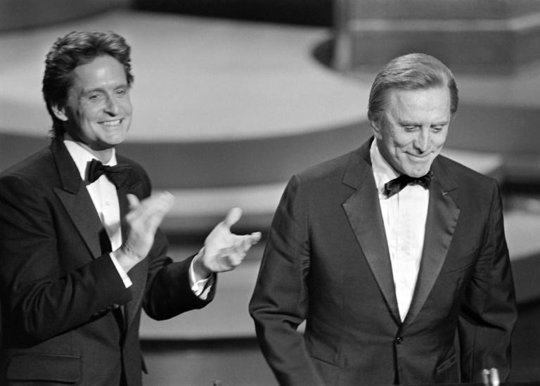 Michael Douglas (L) applauds his father Kirk Douglas during the 57th Annual Academy Awards, in Hollywood in March 1985