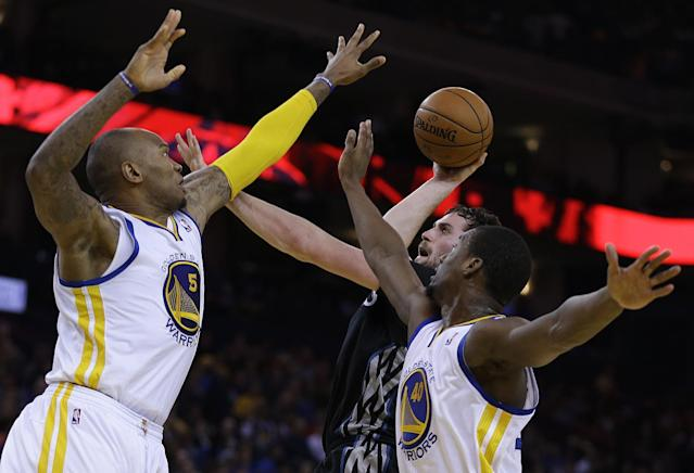 Minnesota Timberwolves' Kevin Love, center, shoots against Golden State Warriors' Marreese Speights, left, and Harrison Barnes, right, during the second half of an NBA basketball game Friday, Jan. 24, 2014, in Oakland, Calif. (AP Photo/Ben Margot)