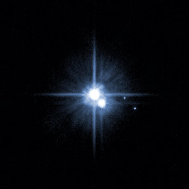 FILE - In this file image provided by NASA  Feb. 22, 2006 from NASA's Hubble Space Telescope shows Pluto and three of it's moons.  A team of scientists using the Hubble Space Telescope said Wednesday, July 11, 2012,  they have discovered the tiniest moon yet around Pluto. That brings the number of known moons to five. (AP Photo/NASA,File)